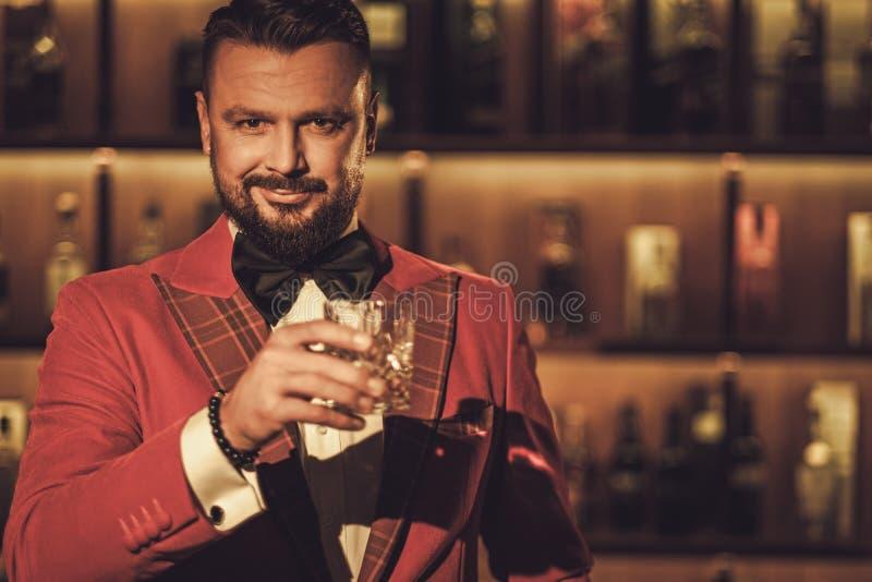 Uomo alla moda esagerato con il vetro del whiskey nel club del signore immagini stock libere da diritti