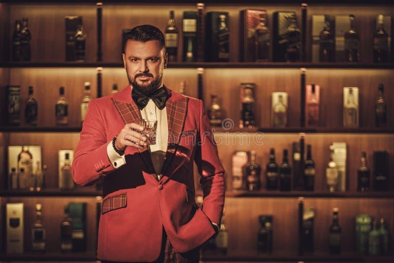 Uomo alla moda esagerato con il vetro del whiskey nel club del signore fotografia stock