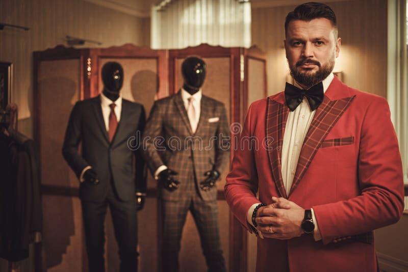 Uomo alla moda esagerato nello studio del sarto fotografia stock