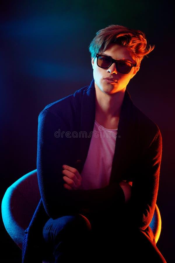 Uomo alla moda fresco in rivestimento ed occhiali da sole neri Modello maschio di alta moda alle luci al neon luminose variopinte fotografia stock