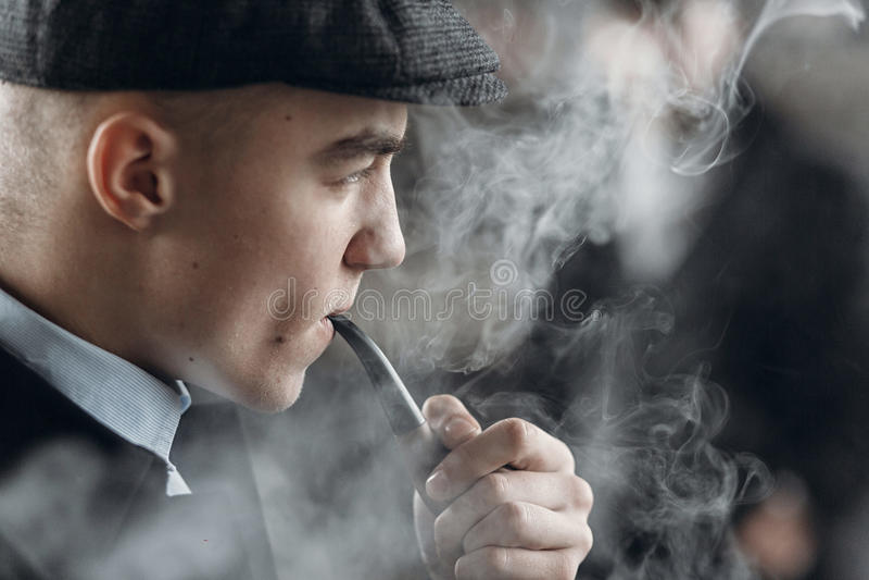 Uomo alla moda in retro attrezzatura, tubo di legno di fumo holme dello sherlock immagini stock