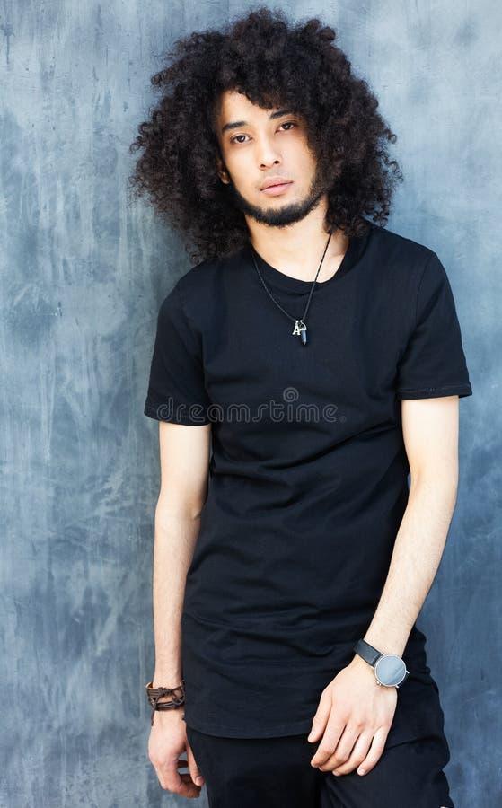 Uomo alla moda vestito in un'attrezzatura nera fresca che posa sulla via Giovane modo, Streetstyle fotografia stock
