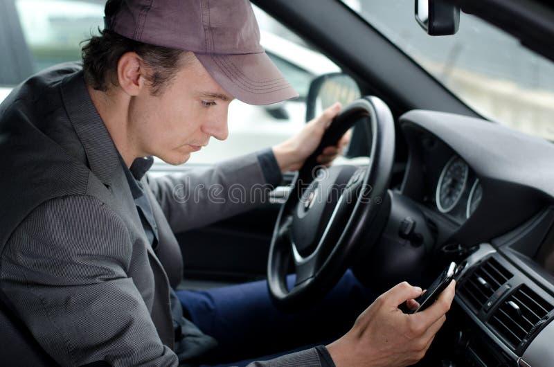 Uomo alla ruota facendo uso del telefono cellulare delle cellule mentre conducendo automobile immagini stock libere da diritti