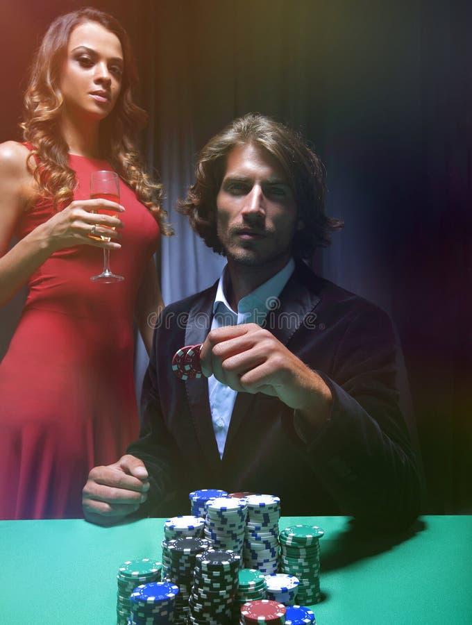 Uomo alla tavola delle roulette circondata dalle belle donne immagini stock