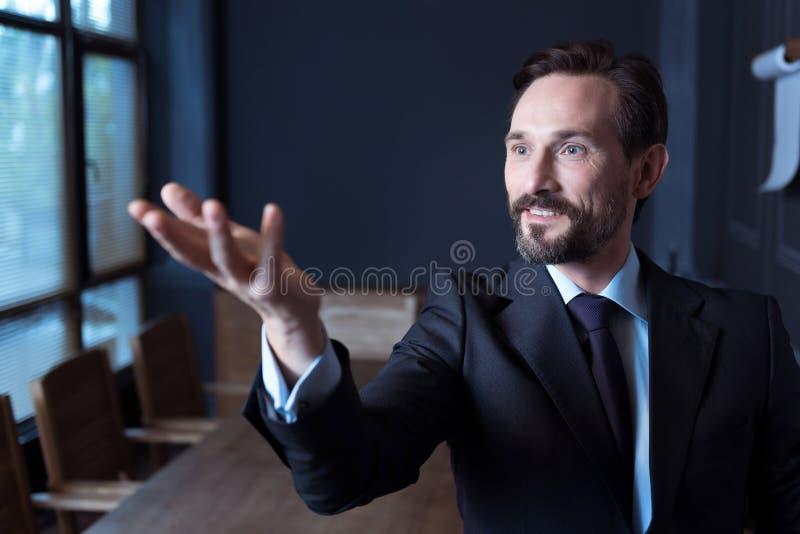 Uomo allegro bello che esamina la sua mano immagini stock