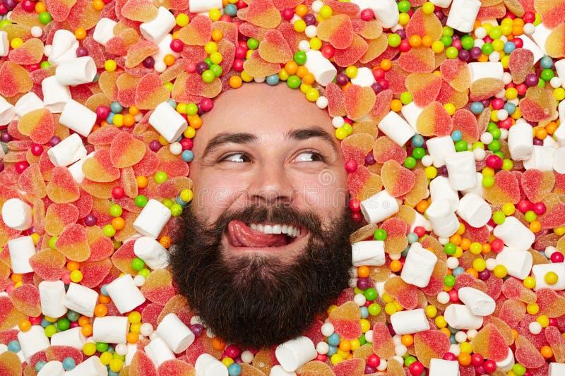 Uomo allegro che gode dei dolci fotografia stock