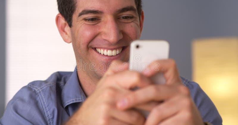 Uomo allegro che manda un sms sullo smartphone fotografia stock libera da diritti