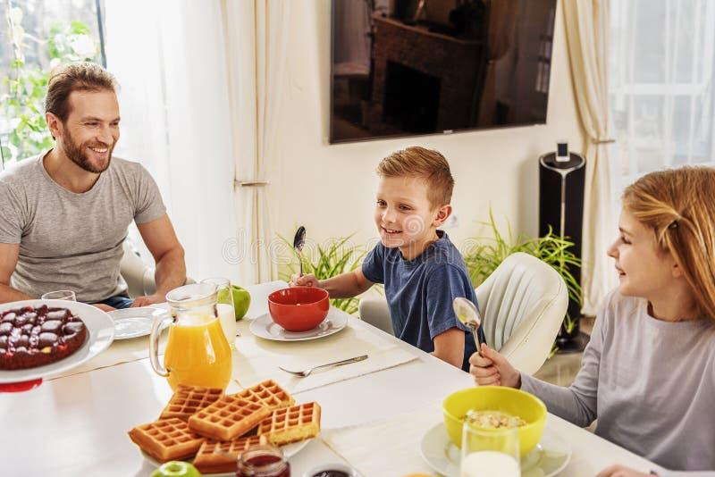 Uomo allegro che mangia prima colazione con i suoi bambini fotografia stock