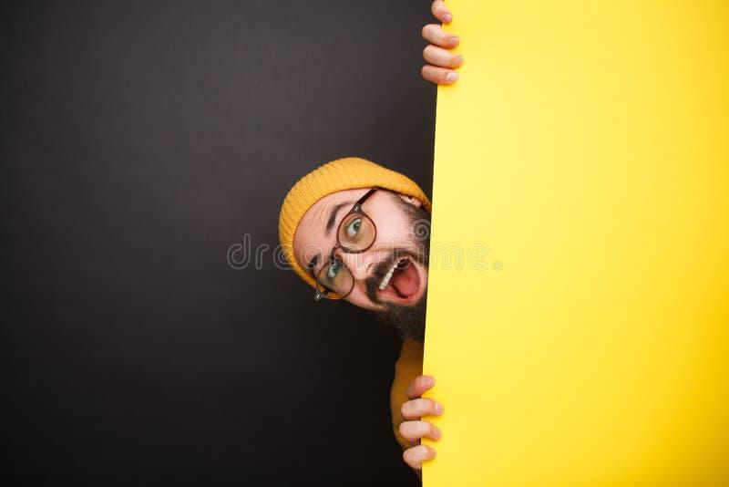Uomo allegro che si nasconde dietro l'insegna gialla immagine stock