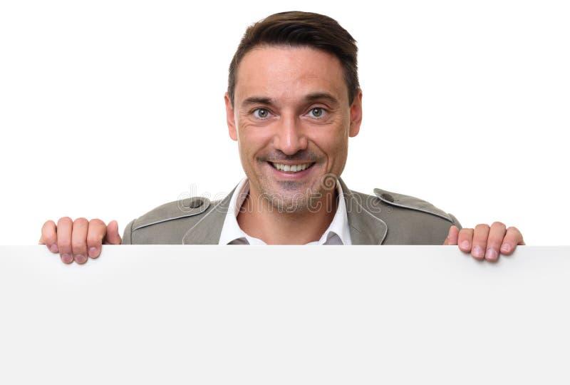 Uomo allegro che sta dietro un tabellone per le affissioni in bianco fotografia stock