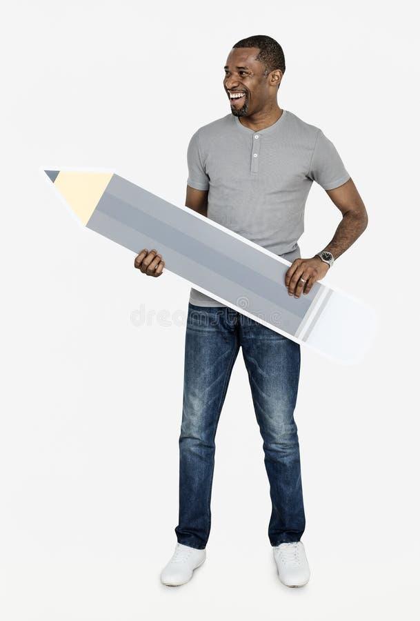 Uomo allegro che tiene un'icona della matita fotografia stock libera da diritti