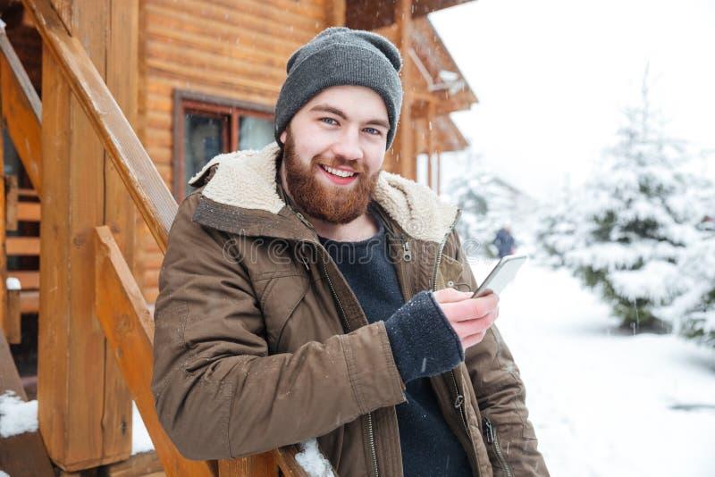 Uomo allegro che utilizza smartphone all'aperto nell'inverno fotografie stock libere da diritti