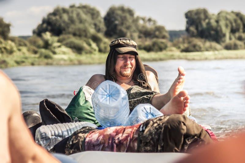 Uomo allegro con il sorriso di piacere e gli occhi chiusi che si rilassano all'aperto durante le vacanze estive immagine stock libera da diritti