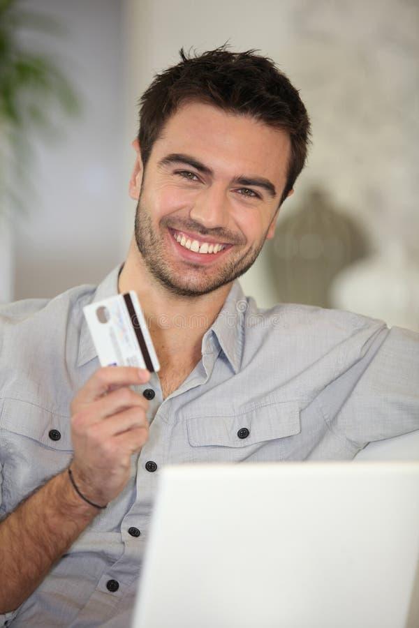 Uomo allegro con la carta di credito fotografia stock