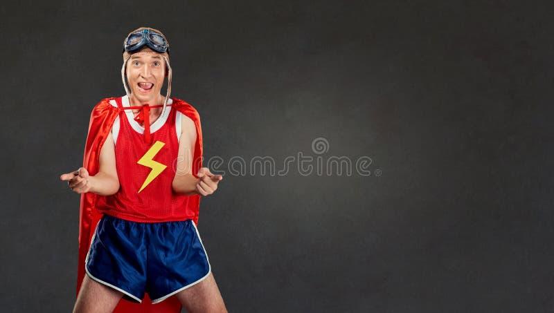 Uomo allegro divertente divertente in un costume del supereroe fotografia stock