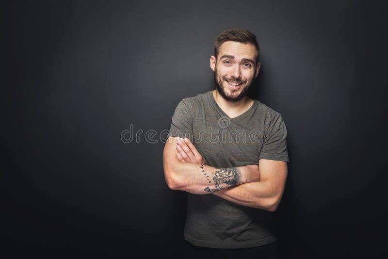 Uomo allegro e bello su un fondo nero immagini stock