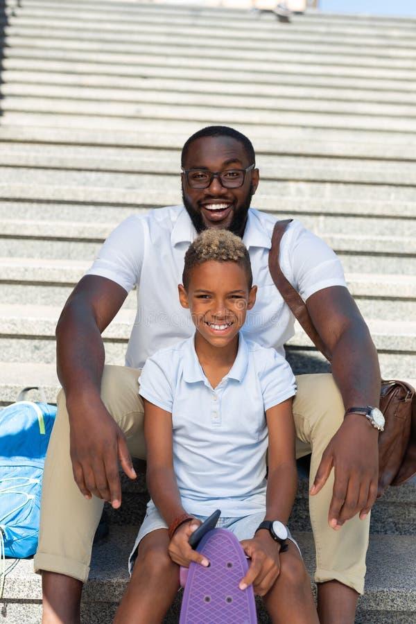 Uomo allegro positivo che si siede dietro suo figlio fotografia stock libera da diritti