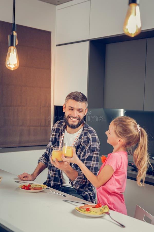Uomo alto barbuto in una camicia a quadretti e la sua sensibilità sveglia della figlia meravigliosa immagini stock libere da diritti