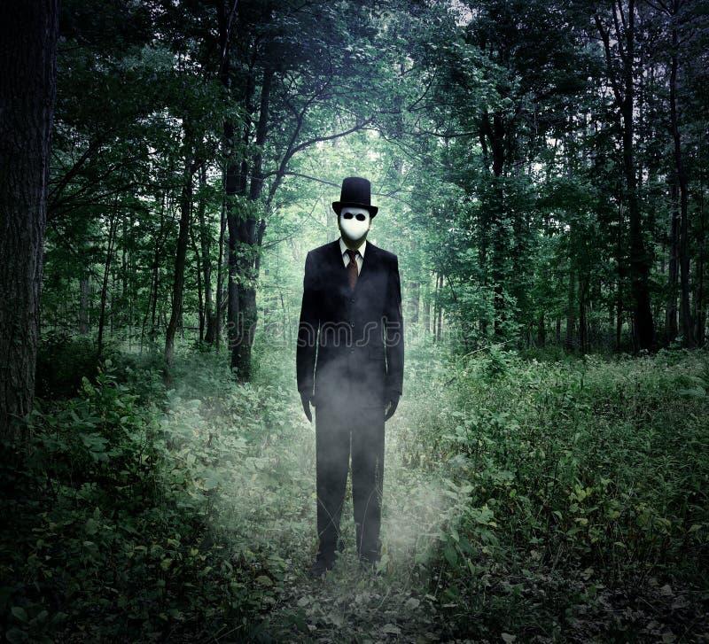 Uomo alto diabolico che sta in legno spaventoso da solo fotografie stock