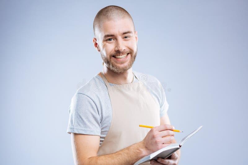 Uomo amichevole allegro felice che tiene il suo taccuino immagine stock