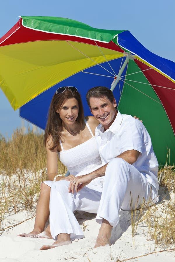 Uomo & donna sotto l'ombrello variopinto sulla spiaggia immagini stock libere da diritti