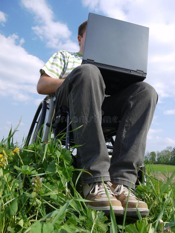uomo andicappato del computer portatile fotografia stock