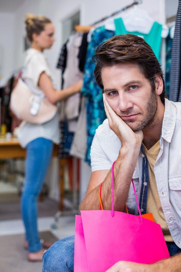 Uomo annoiato con i sacchetti della spesa che si siedono davanti alla sua amica fotografia stock libera da diritti