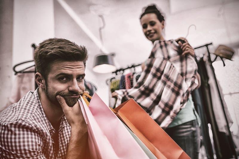 Uomo annoiato con i sacchetti della spesa mentre la donna dai vestiti tormenta immagini stock libere da diritti