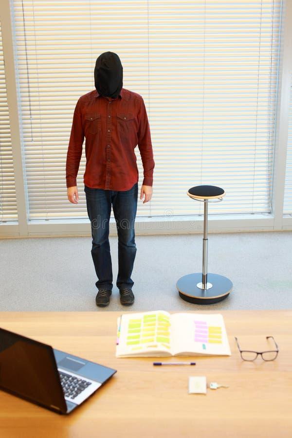 Uomo anonimo in sacco nero sulla testa che sta nell'ufficio fotografia stock