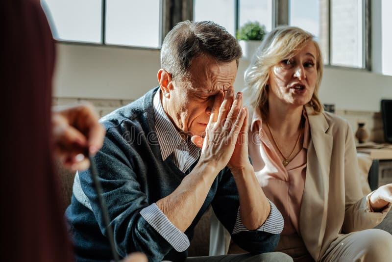 Uomo anziano afflitto che è depresso con la situazione nella sua famiglia fotografia stock libera da diritti