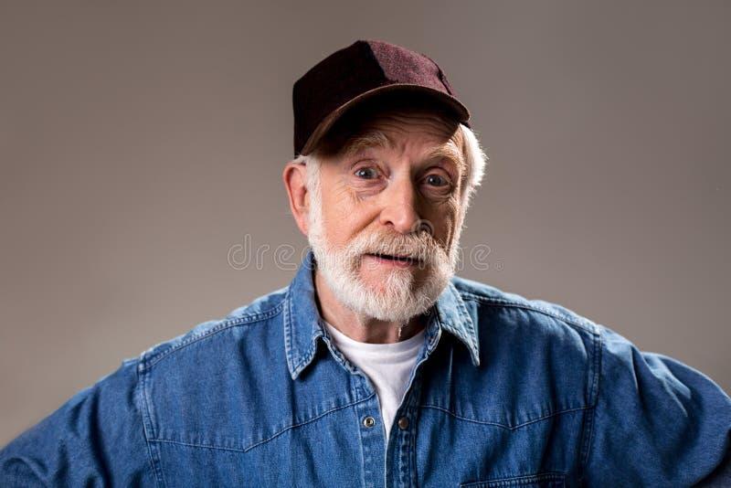 Uomo anziano allegro che guarda con la meraviglia fotografia stock libera da diritti