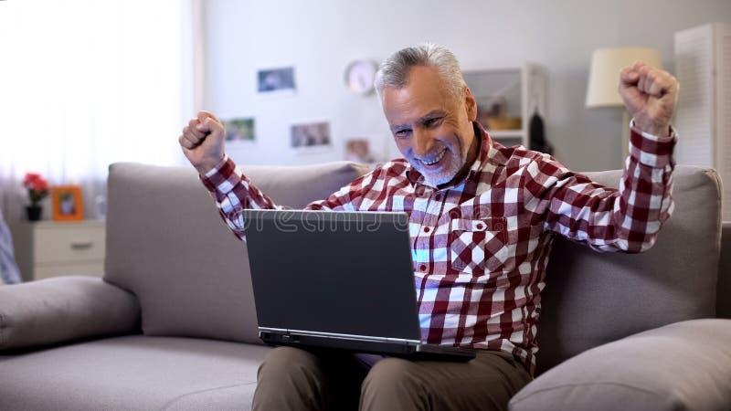 Uomo anziano allegro che ottiene risposta a datare sito, ricevente buone notizie, fortuna immagine stock libera da diritti