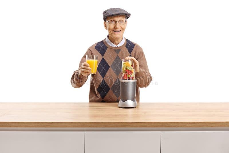 Uomo anziano allegro che prepara frutta in un miscelatore e che tiene un vetro di succo fresco fotografia stock libera da diritti