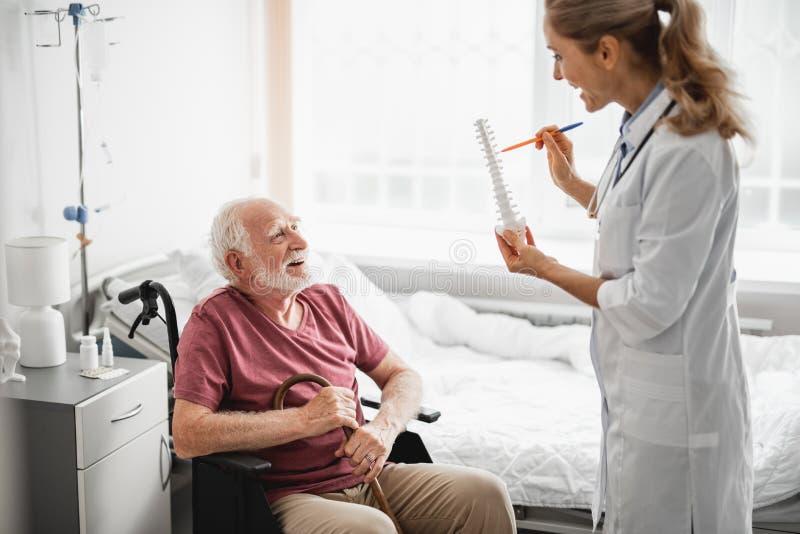 Uomo anziano allegro in medico d'ascolto della sedia a rotelle fotografia stock