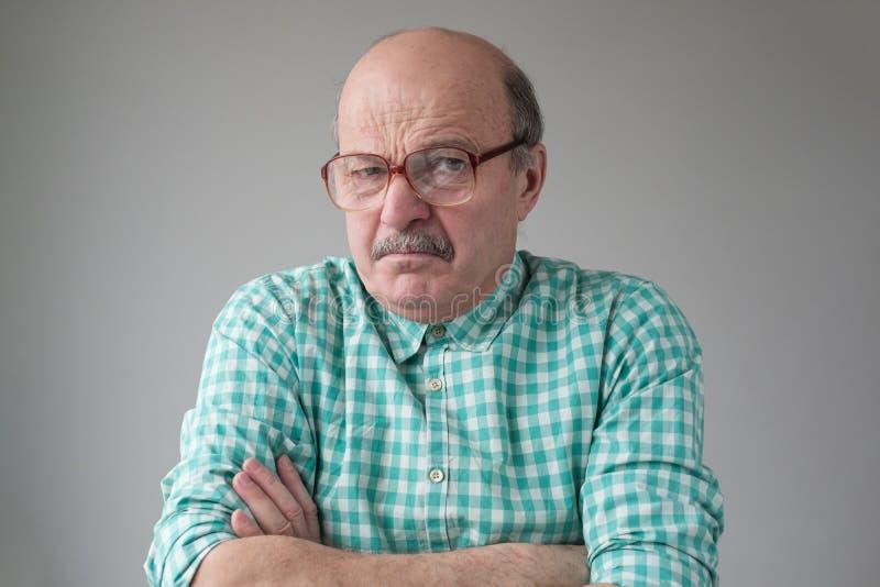 Uomo anziano arrabbiato con gli occhiali che incrociava le braccia che sembrava infastidito dalla telecamera immagini stock libere da diritti