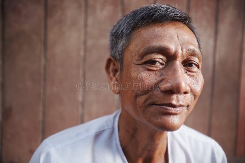 Uomo anziano asiatico che esamina macchina fotografica contro la parete marrone fotografia stock libera da diritti