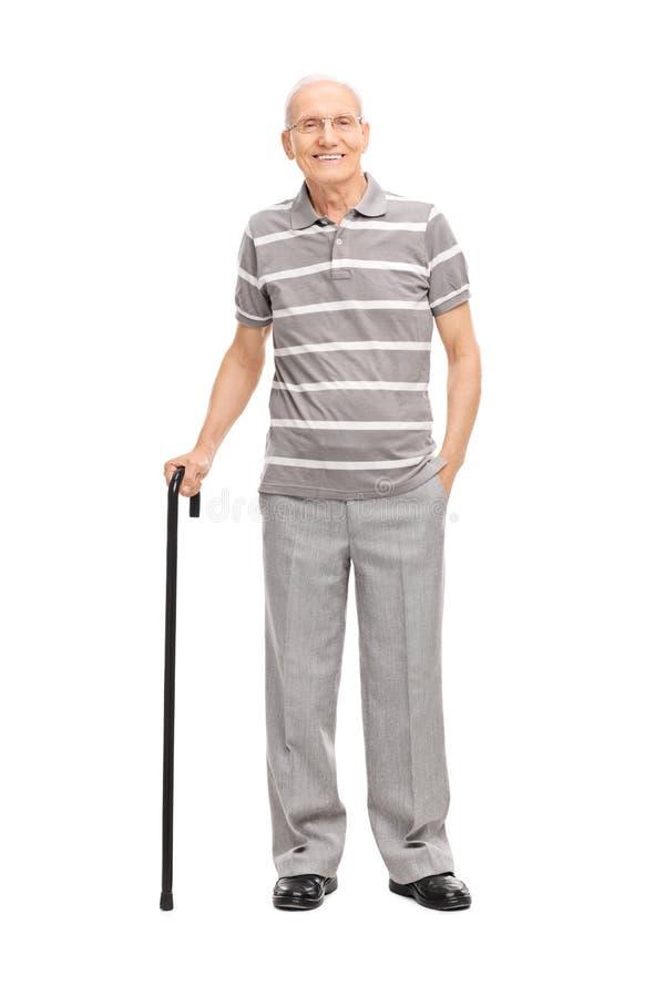Uomo anziano in camicia di polo che tiene una canna e una posa fotografia stock libera da diritti