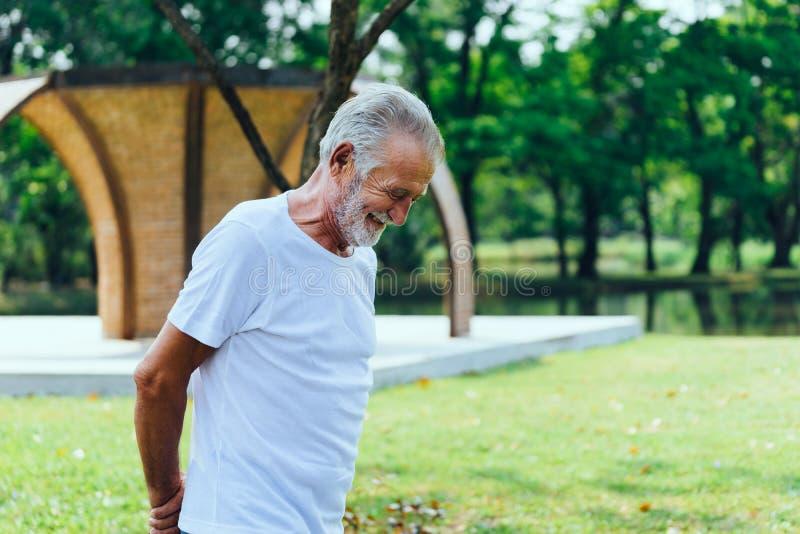 Uomo anziano caucasico in maglietta bianca che cammina e che sorride avendo buon umore nel parco immagine stock