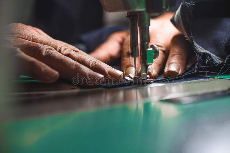 Uomo anziano che adatta vestito su ordinazione facendo uso della vecchia scuola della macchina per cucire fotografia stock libera da diritti