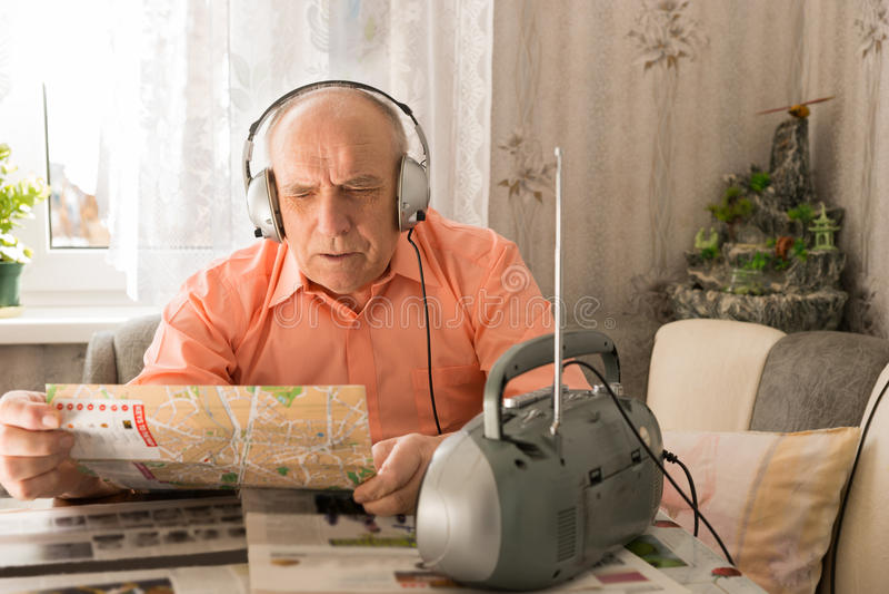 Uomo anziano che ascolta dalla radio mentre leggendo tabloid fotografia stock