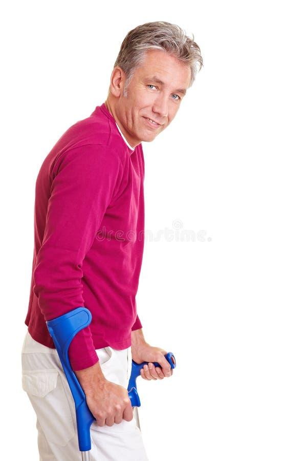 Uomo anziano che cammina con le grucce fotografia stock libera da diritti