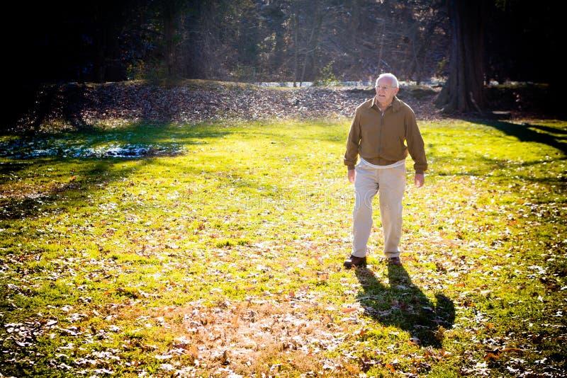 Uomo anziano che cammina fuori nella caduta fotografia stock
