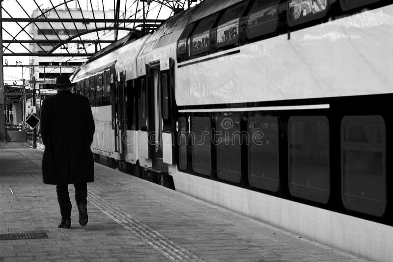Uomo anziano che cammina lungo un treno di un binario vuoto che sta viaggiando o detto gli arrivederci a qualcuno - BW fotografie stock