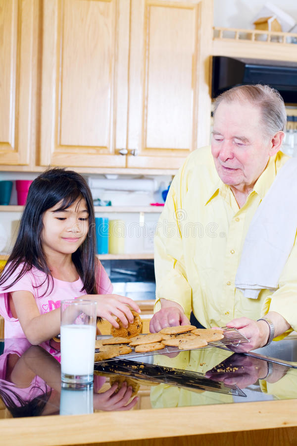 Uomo anziano che divide i biscotti con la nipote immagini stock
