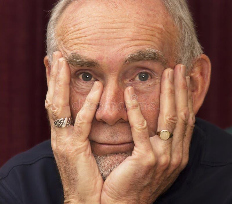 Uomo anziano che fissa nello spazio con il mento in mani