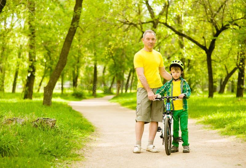 Uomo anziano che insegna al suo nipote a guidare una bici fotografia stock