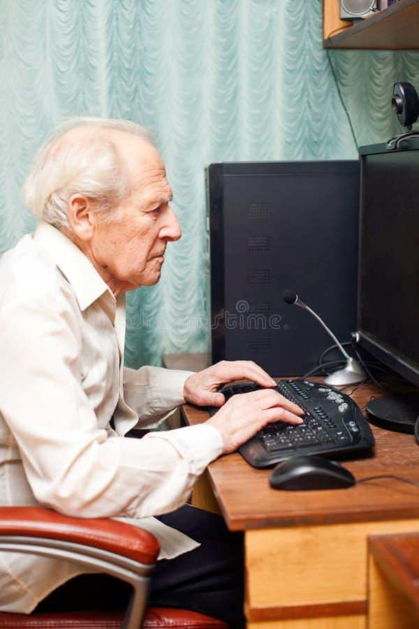 Uomo anziano che lavora al calcolatore immagini stock libere da diritti