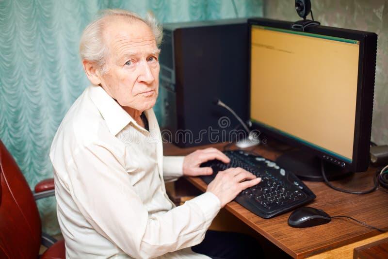 Uomo anziano che lavora al calcolatore fotografie stock