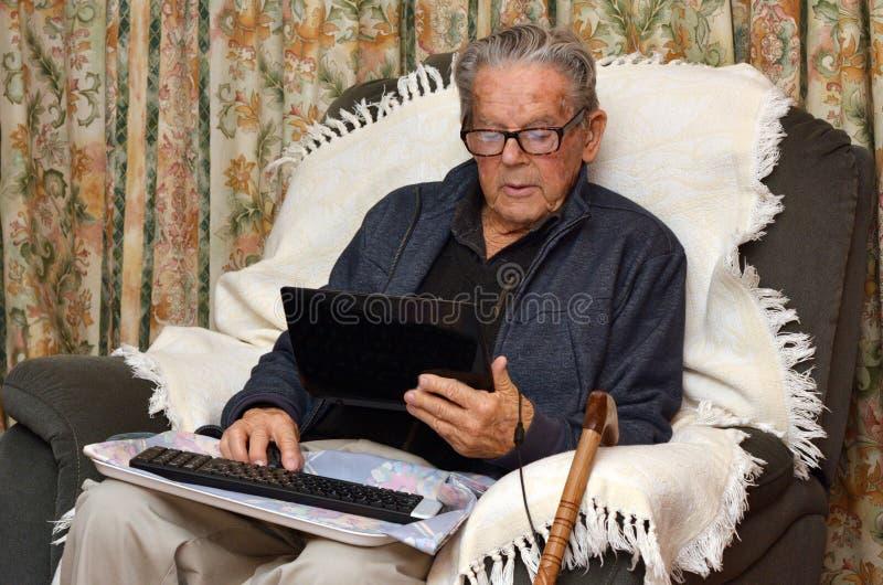 Uomo anziano che lavora con il computer portatile a casa immagini stock libere da diritti