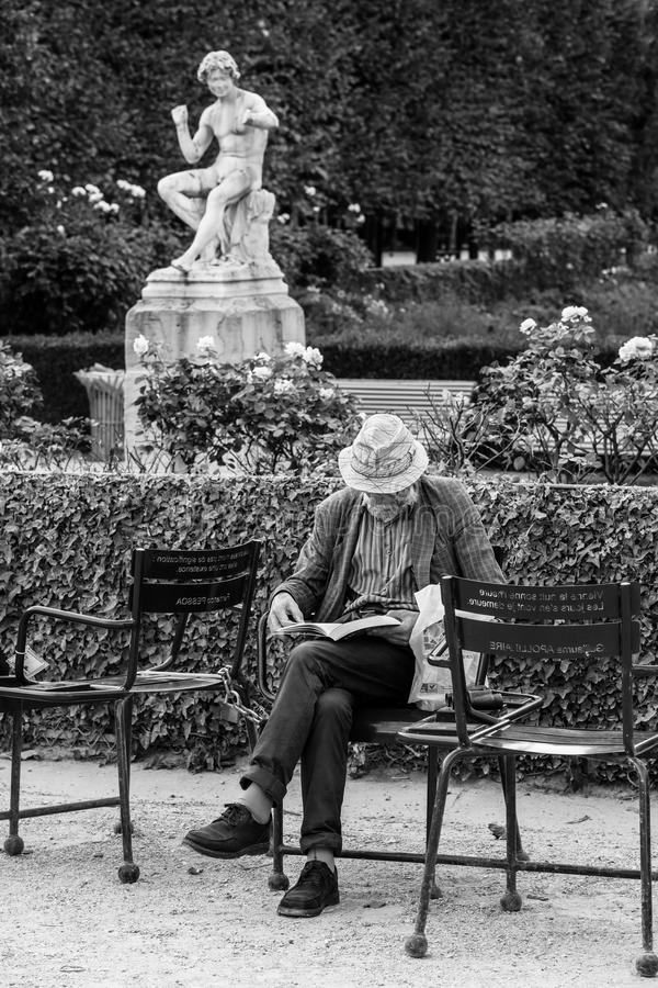 Uomo anziano che legge un libro fuori nel cortile dell'amico reale fotografia stock